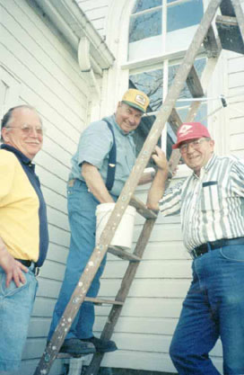 Three men from our church working outside with a ladder.